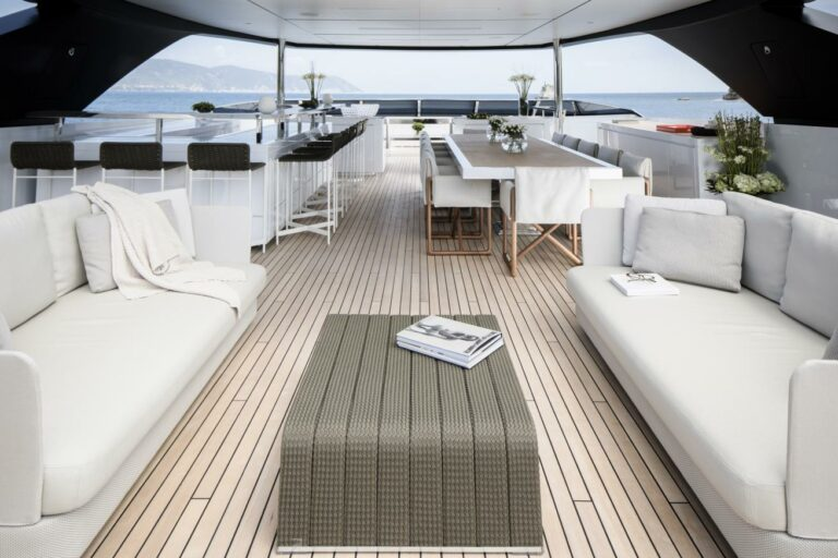 Flybridge luxury yacht SEVEN SINS spacious deck for charter loung and dining white and grey design